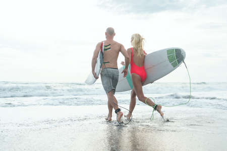 Young people with a surfboards outdoors
