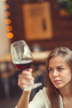 Young girl with a wine glass indoors