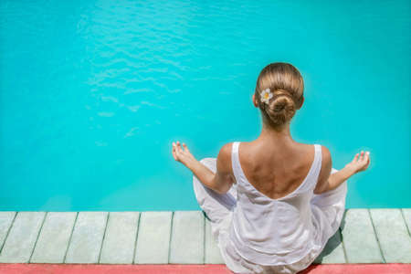 Young girl in a lotus pose by the pool