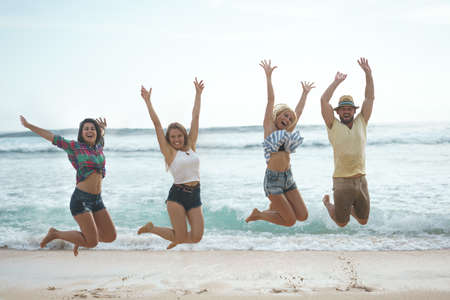 Happy jumping people on the beach