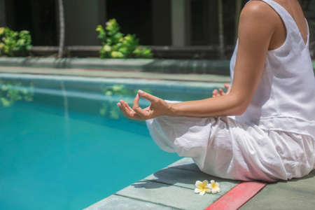 Young girl doing yoga by the pool