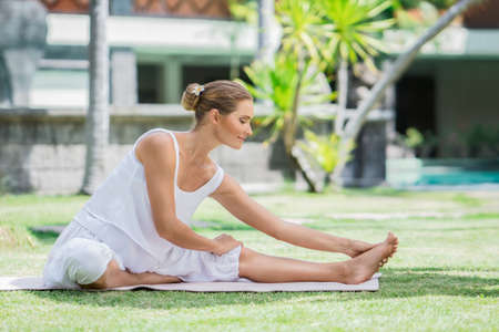 Young woman doing yoga on a lawn