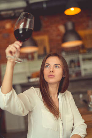 Young sommelier with a glass of red wine in a restaurant
