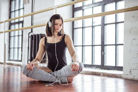 Young girl with music headhones in dance studio