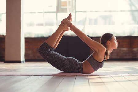 Attractive woman practicing yoga in the loft