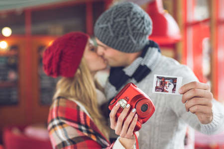 Kissing couple with a red instant camera indoors