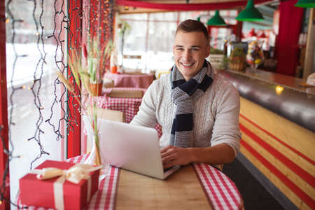 Smiling young man with laptop in a cafe