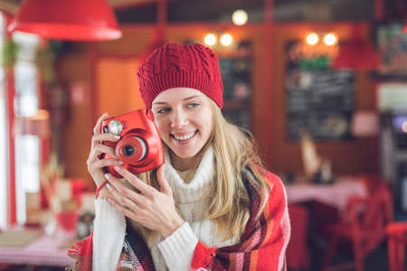 Smiling attractive woman with a red instant camera indoors Reklamní fotografie