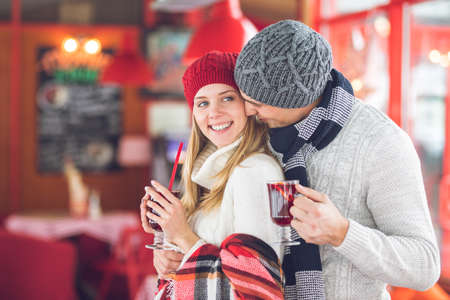 Young couple with glasses of mulled wine at Christmas