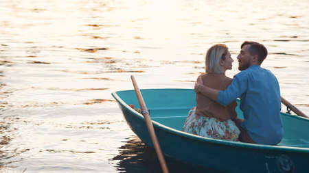 Embracing young couple in a boat at the lake