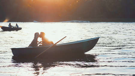 Kissing couple in a boat at sunset