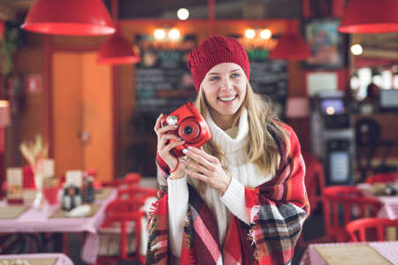 Happy attractive woman with a red instant camera indoors