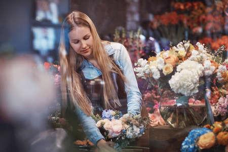 Aantrekkelijk meisje in uniforn in een bloemenwinkel