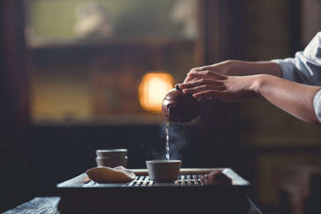 Young girl pouring tea from teapot close-up
