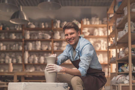 Smiling young man with a potters wheel