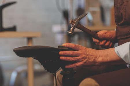 An elderly shoemaker at work close-up