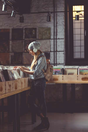Young girl listening to music in a vinyl record store Stock Photo