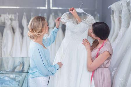 Un vendedor joven y el cliente con un vestido de novia Foto de archivo - 102060713