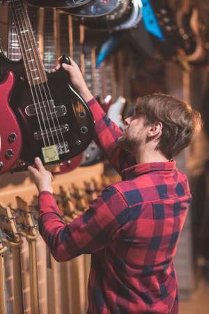 Young musician choosing a bass guitar