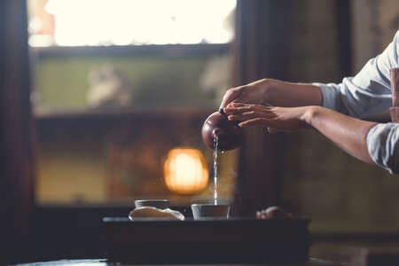 Womens hands pouring tea