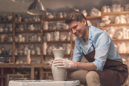 Young man at a potters wheel indoors