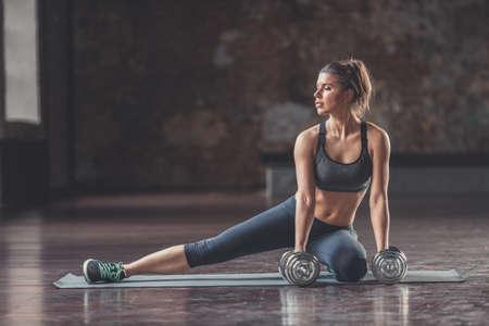 Atletische jonge vrouw met een halter
