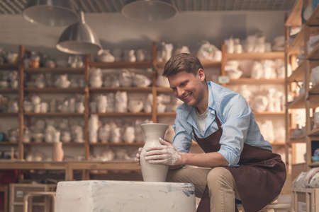 Young man behind a potters wheel