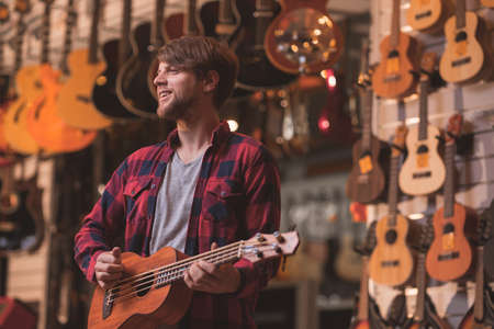 Smiling musician with a ukulele in a music store 写真素材