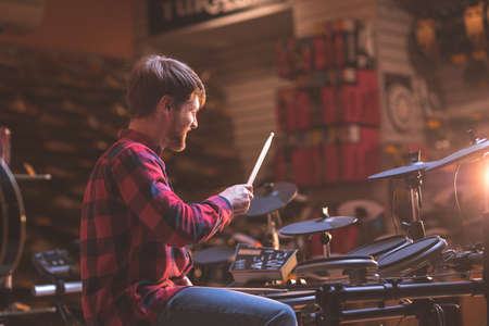 Young man playing drums in a music store