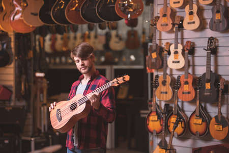 Young musician with a guitar in a store