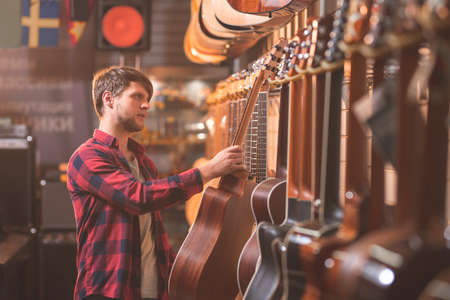Young musician choosing a guitar in a store