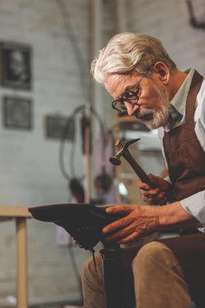 An elderly shoemaker in a studio 写真素材
