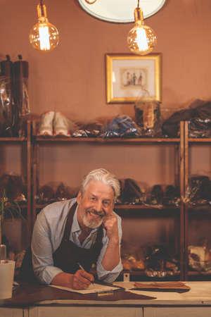 Smiling elderly shoemaker indoors
