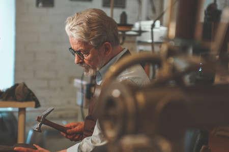 An elderly shoemaker at work Zdjęcie Seryjne - 103906323