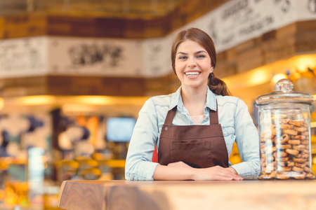 Attractive baker in uniform at the counter