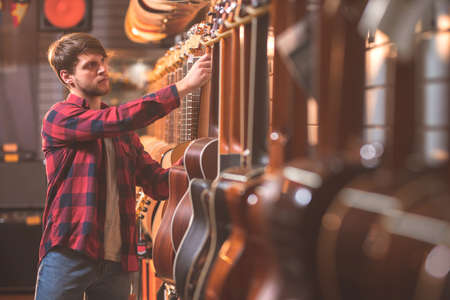 Young musician with a guitar indoors