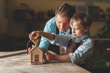 Father and son with a wooden house indoors Imagens