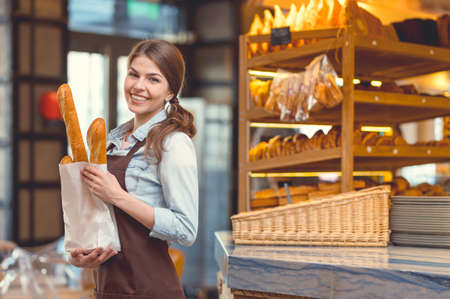 Young smiling girl with baguettes