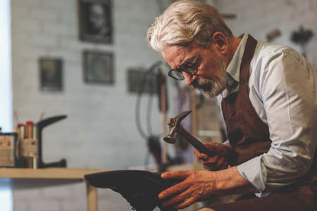 An elderly shoemaker in uniform at work Zdjęcie Seryjne