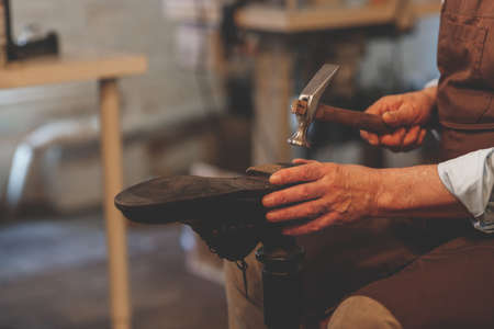 An elderly shoemaker at work