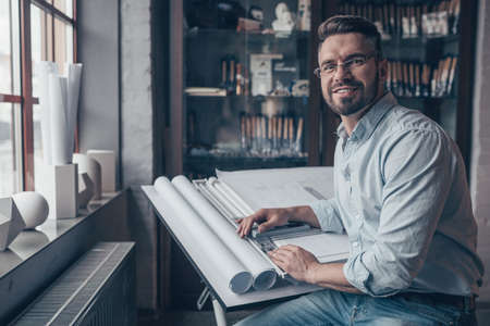 Smiling mature man with drawing Reklamní fotografie