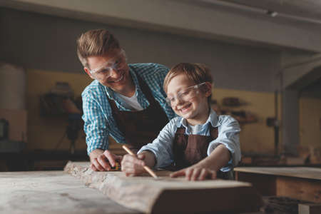 Smiling father and son with glasses at work