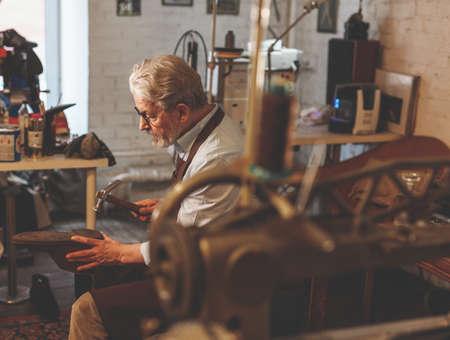 An elderly shoemaker at work
