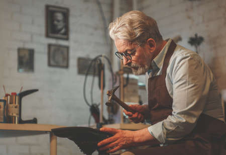 An elderly shoemaker in the workshop