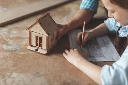 Little boy with a wooden house