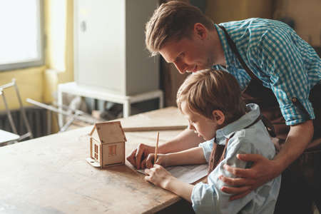 Father and son with a wooden house