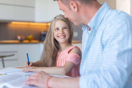 Young father and smiling daughter doing homework