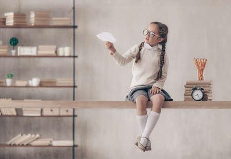 Kleines Schulmädchen mit einem Papierflugzeug