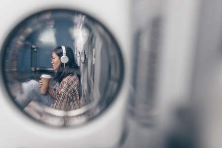 Young girl with coffee in the laundry