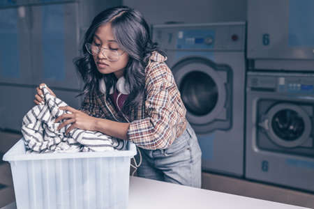Attractive woman with a basket in laundry